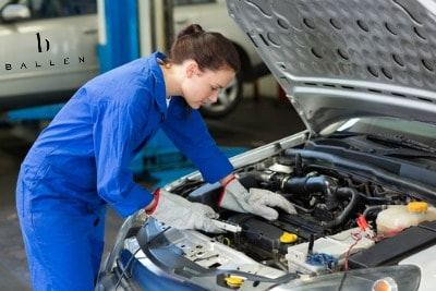 woman-mechanic-working-under-hood-of-car